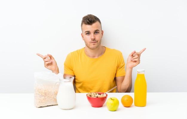 Jonge blonde man aan het ontbijt te wijzen op de laterale twijfels
