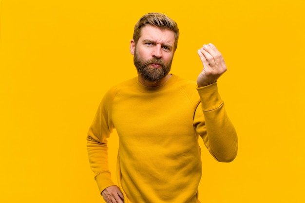 Jonge blonde man die capice of geldgebaar maakt en je zegt dat je je schulden moet betalen! tegen oranje muur