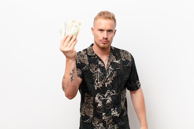 Jonge blonde man die capice of geldgebaar maakt en je zegt dat je je schulden moet betalen! tegen witte muur met bankbiljetten