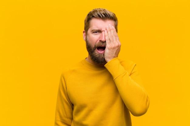 Jonge blonde man die slaperig, verveeld en geeuwend kijkt, met hoofdpijn en een hand die de helft van het gezicht bedekt