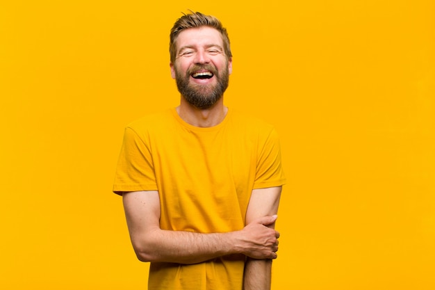 Jonge blonde man die verlegen en vrolijk lacht, met een vriendelijke en positieve maar onzekere houding