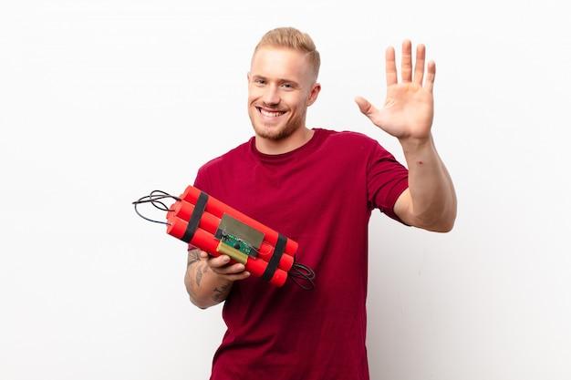Jonge blonde man die vrolijk en opgewekt glimlacht, hand zwaait, je verwelkomt en begroet, of afscheid neemt tegen een witte muur met een dynamietexplosief