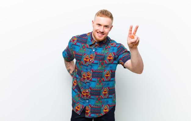 Jonge blonde man draagt een cool shirt glimlachen en kijken gelukkig, zorgeloos en positief, gebaren overwinning of vrede met één hand tegen witte muur