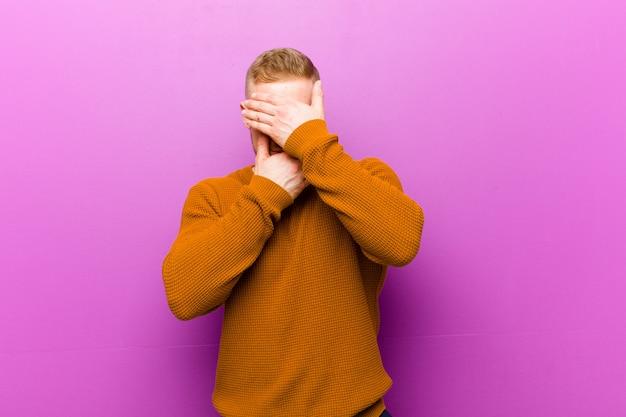 Jonge blonde man draagt een trui die het gezicht bedekt met beide handen en nee zegt tegen de camera! afbeeldingen weigeren of foto's verbieden
