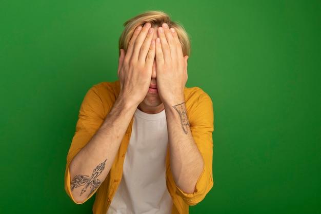 Jonge blonde man draagt geel t-shirt bedekt gezicht met handen geïsoleerd op groen met kopie ruimte