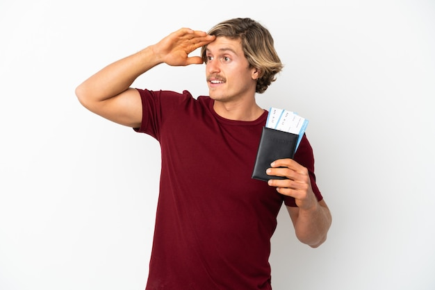 Jonge blonde man geïsoleerd in vakantie met paspoort en vliegtickets