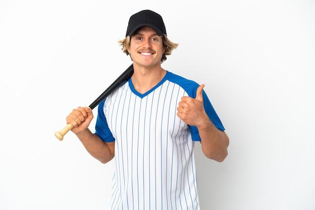Jonge blonde man geïsoleerd op een witte achtergrond honkbal spelen en met duimen omhoog omdat er iets goeds is gebeurd