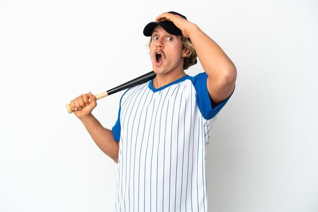Jonge blonde man honkbal spelen geïsoleerd op een witte achtergrond doet verrassing gebaar terwijl het kijken naar de zijkant