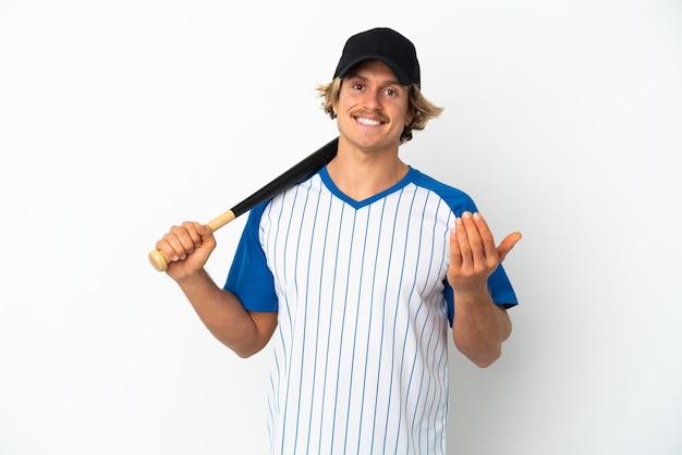 Jonge blonde man honkbal spelen geïsoleerd op een witte achtergrond uitnodigend om met de hand te komen. blij dat je gekomen bent