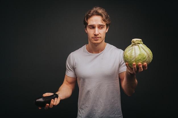 Jonge blonde man in wit t-shirt houdt aubergine en kool met teleur