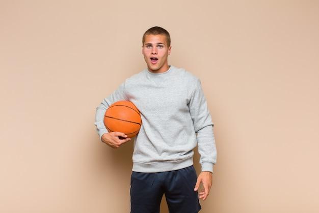 Jonge blonde man kijkt erg geschokt of verrast, starend met open mond en zegt wow
