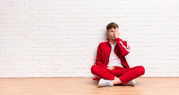 Jonge blonde man kijkt slaperig, verveeld en geeuwend, met hoofdpijn en één hand die de helft van het gezicht bedekt, zittend op de vloer