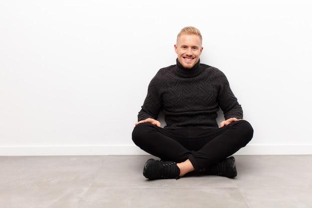 Jonge blonde man lacht vrolijk en terloops met een positieve, gelukkige, zelfverzekerde en ontspannen expressie zittend op cementvloer