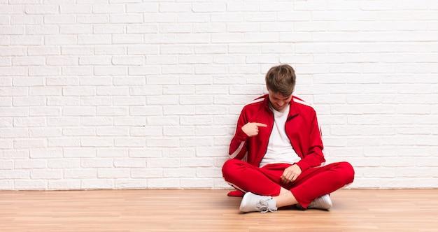 Jonge blonde man lacht vrolijk en terloops, naar beneden kijkend en wijst naar de borst zittend op de vloer