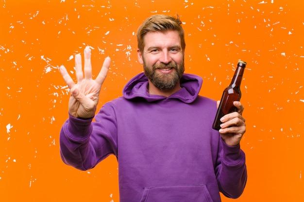 Jonge blonde man met een biertje draagt een paarse hoodie tegen beschadigde oranje muur