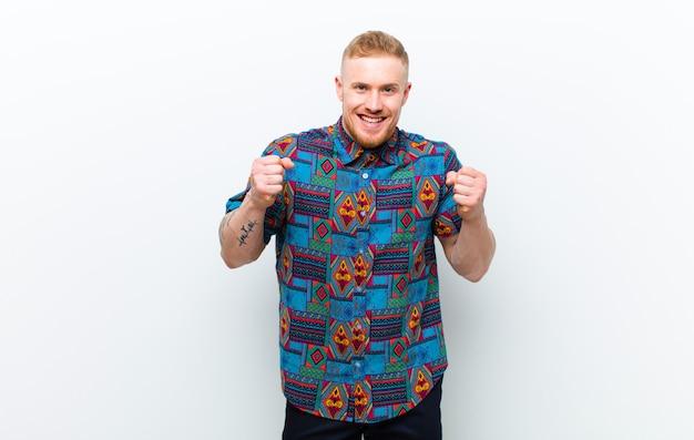Jonge blonde man met een cool shirt die zich geschokt, opgewonden en gelukkig voelt, lacht en succes viert en wow zegt! tegen witte muur