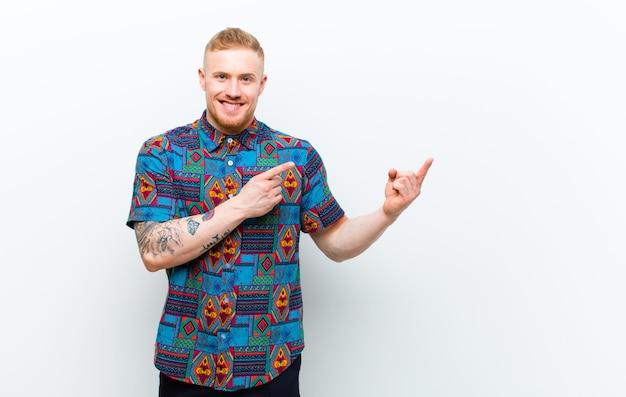 Jonge blonde man met een cool shirt glimlachen, genieten van het leven, zich gelukkig, vriendelijk, tevreden en zorgeloos voelen met de hand op de kin tegen de witte muur