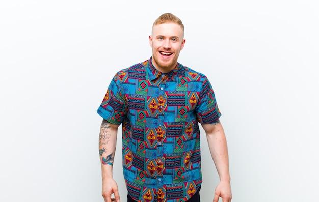Jonge blonde man met een cool shirt op zoek gelukkig en goofy met een brede, leuke, gekke glimlach en ogen wijd open tegen de witte muur