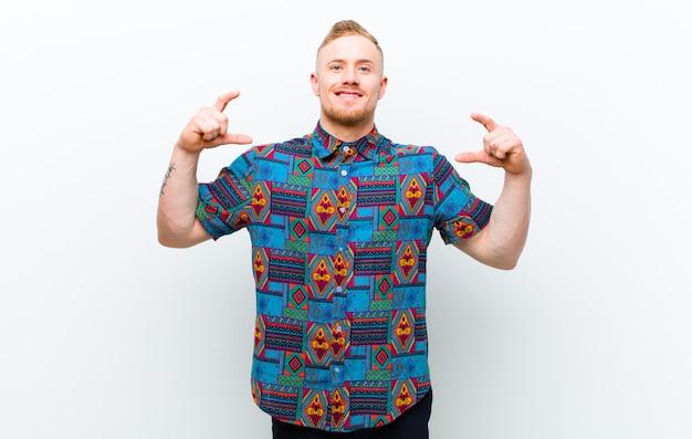 Jonge blonde man met een cool shirt op zoek gelukkig, trots en verrast, vrolijk naar zichzelf wijzend, zelfverzekerd en verheven over de witte muur