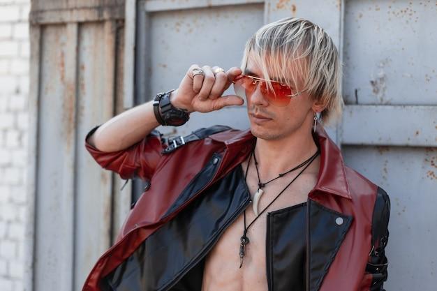 Jonge blonde man met een naakte torso in een trendy leren jas in een stijlvolle rode zonnebril met amuletten om een nek vormt op straat in de buurt van een vintage grijs metalen gebouw.