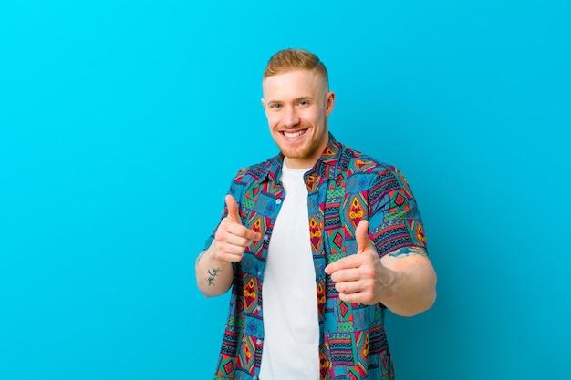 Jonge blonde man met een print shirt blij, cool, tevreden, ontspannen en succesvol gevoel, het kiezen van jou