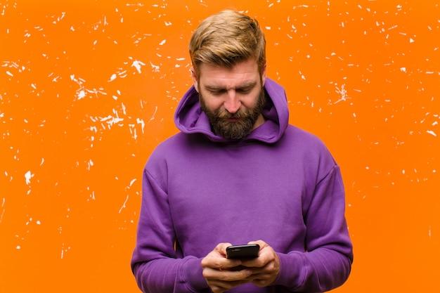 Jonge blonde man met een slimme telefoon draagt een paarse hoodie beschadigde oranje muur