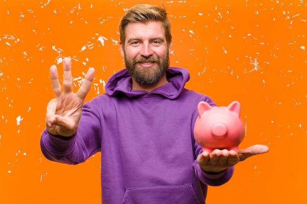 Jonge blonde man met een spaarvarken draagt een paarse hoodie tegen beschadigde oranje muur