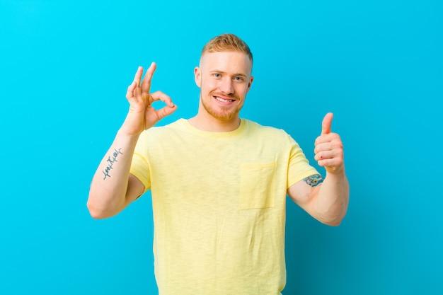 Jonge blonde man met gele t-shirt voelt zich gelukkig, verbaasd, tevreden en verrast, toont goed en beduimelt omhoog gebaren, glimlachend