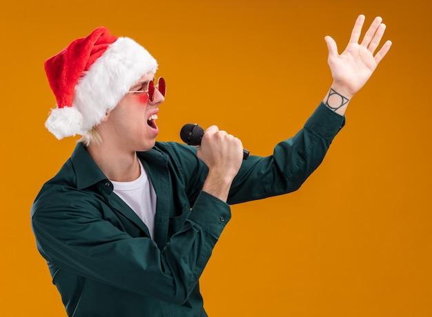 Jonge blonde man met kerstmuts en bril met microfoon die naar de zijkant kijkt en hand in de lucht zingt geïsoleerd op oranje achtergrond orange