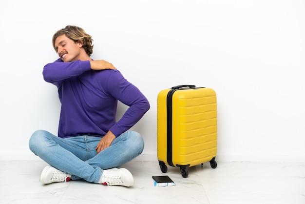 Jonge blonde man met koffer zittend op de vloer die lijdt aan pijn in de schouder omdat hij zich heeft ingespannen