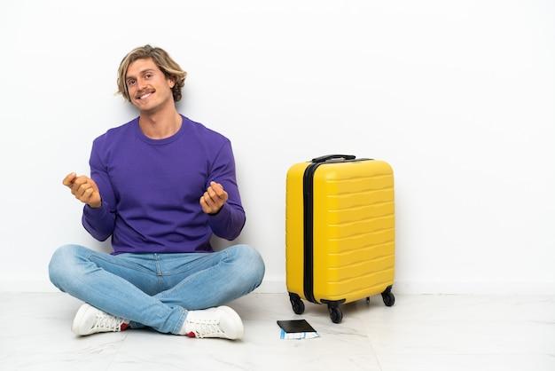 Jonge blonde man met koffer zittend op de vloer geld gebaar maken