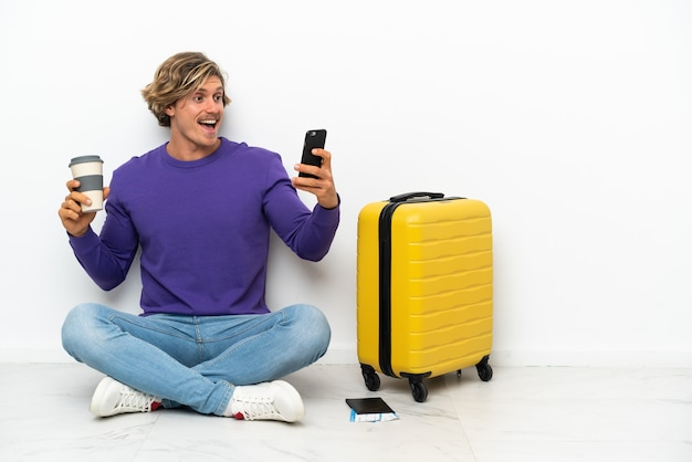 Jonge blonde man met koffer zittend op de vloer koffie te houden om mee te nemen en een mobiel