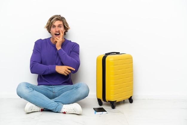 Jonge blonde man met koffer zittend op de vloer verrast en geschokt terwijl hij naar rechts kijkt
