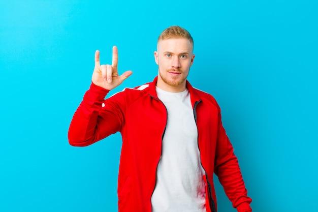 Jonge blonde man met sportkleding voelt zich gelukkig, leuk, zelfverzekerd, positief en opstandig, waardoor rock of heavy metal met de hand ondertekenen