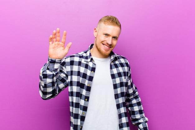 Jonge blonde man met vierkant shirt glimlachend gelukkig en vrolijk, zwaaiende hand, verwelkomen en begroeten, of afscheid