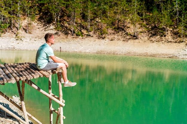 Jonge blonde man op een brug boven een bergmeer met helder water en uitzicht op een groen bos