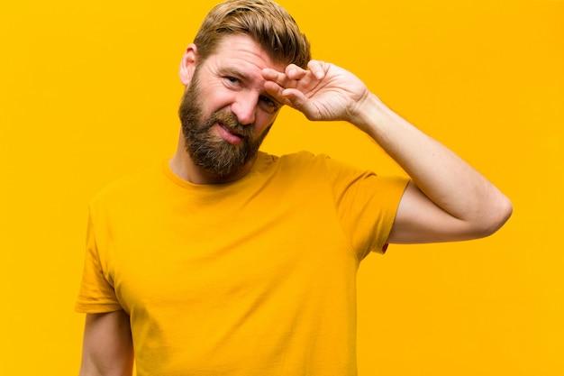 Jonge blonde man op zoek gestrest, moe en gefrustreerd, drogen zweet van het voorhoofd, voelen zich hopeloos en uitgeput tegen de oranje muur