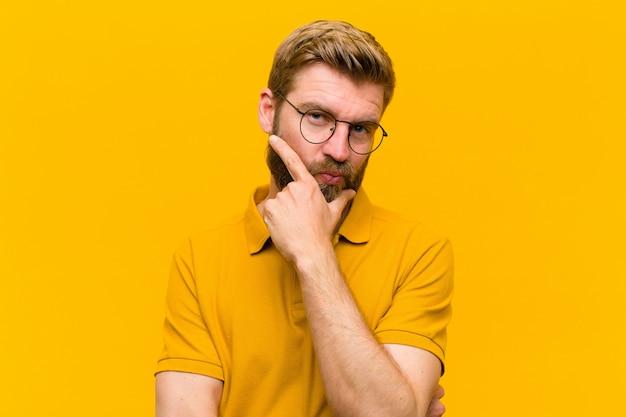 Jonge blonde man op zoek serieus, attent en wantrouwend, met één arm gekruist en hand op kin, weging opties