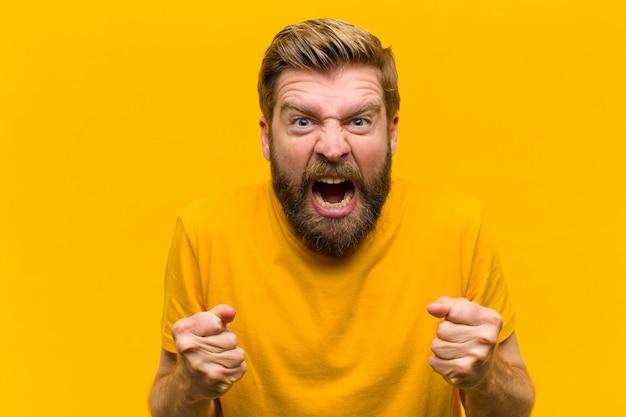 Jonge blonde man schreeuwt agressief met geërgerd, gefrustreerd, boos uiterlijk en strakke vuisten, woedend tegen oranje muur