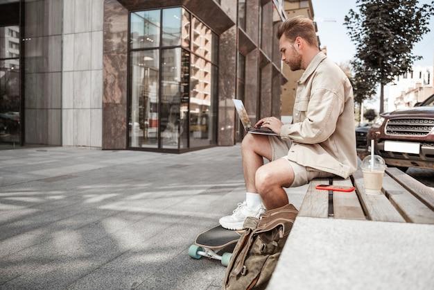 Jonge blonde man skater zittend op een bankje met laptop smartphone online communiceren, streaming met longboard en rugzak afhaalkoffie. onderweg werken op afstand. druk stadsleven. stijlvolle millennial.