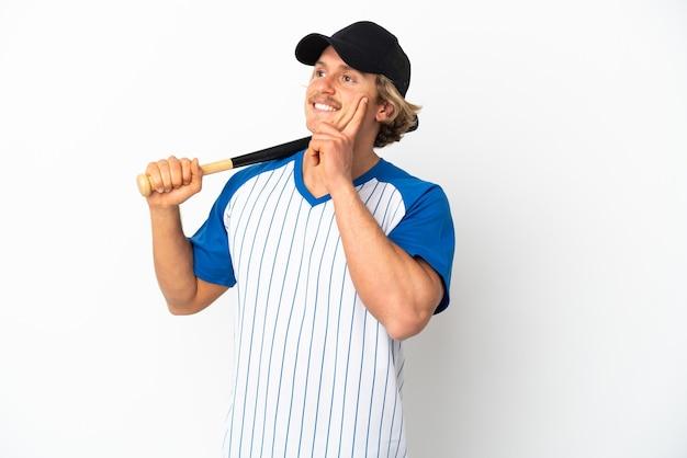 Jonge blonde man spelen honkbal geïsoleerd op een witte achtergrond een idee denken terwijl opzoeken