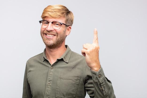 Jonge blonde man trotse uitdrukking. nummer één concept