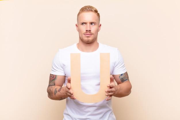 Jonge blonde man verward, twijfelachtig, denken, met de letter u van het alfabet om een woord of zin te vormen.
