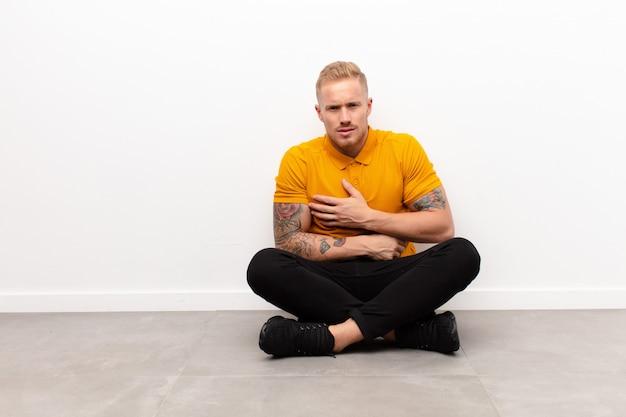 Jonge blonde man voelt zich angstig, ziek, ziek en ongelukkig, lijdt aan een pijnlijke buikpijn of griep zittend op cementvloer