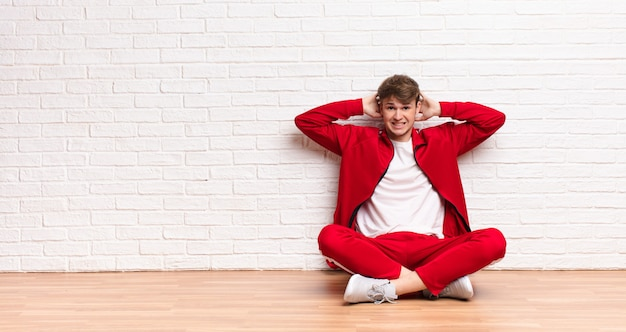 Jonge blonde man voelt zich gestrest, bezorgd, angstig of bang, met de handen op het hoofd, in paniek bij een fout zittend op de vloer