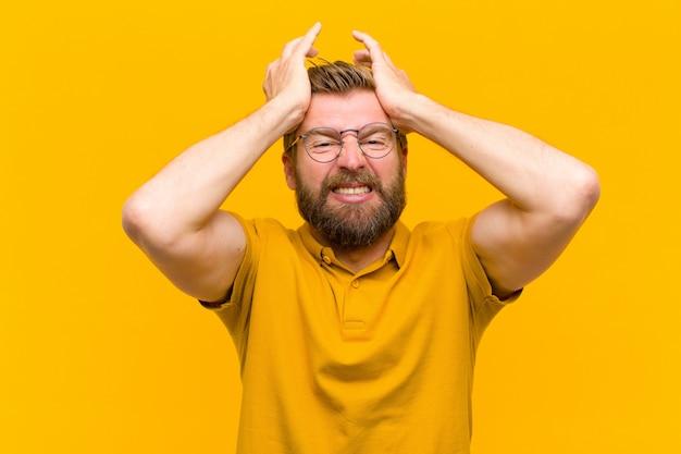 Jonge blonde man voelt zich gestrest en angstig, depressief en gefrustreerd met een hoofdpijn, beide handen opheffend om tegen de oranje muur te gaan