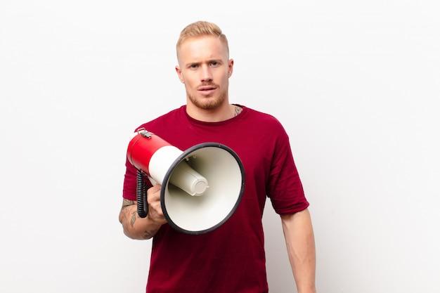 Jonge blonde man voelt zich verbaasd en verward, met een domme, verbijsterde uitdrukking die naar iets onverwachts kijkt tegen een witte muur met een megafoon