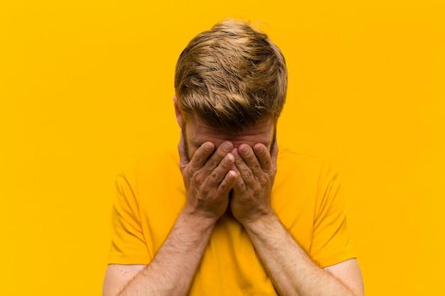 Jonge blonde man voelt zich verdrietig, gefrustreerd, nerveus en depressief, bedekkend gezicht met beide handen, huilend tegen oranje muur