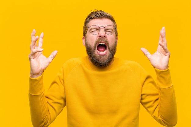 Jonge blonde man woedend schreeuwen, gestrest en geïrriteerd voelen met handen omhoog in de lucht zeggen waarom ik oranje muur