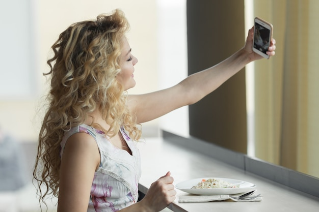 Jonge blonde meid die zelfportret maakt op haar smartphone digitale camera terwijl ze tijdens de lunchpauze in café zit.